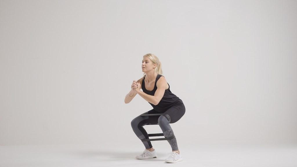 Øvelser mot vonde knær: knebøy med strikk